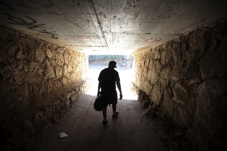 After being deported by U.S. immigration authorities, this young man, who was raised in Santa Barbara, crosses through a highway tunnel in Mexico.