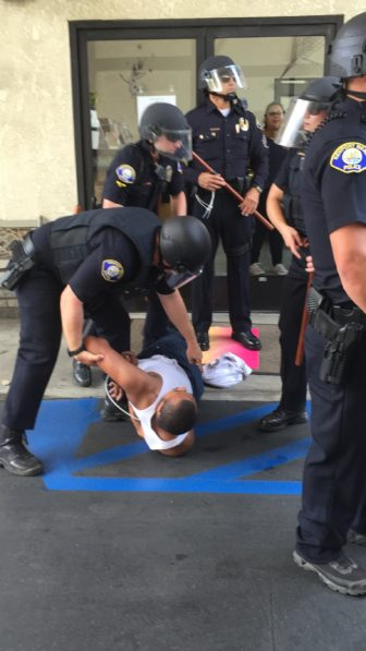 Anaheim police officers arrest a protester outside the Trump rally.