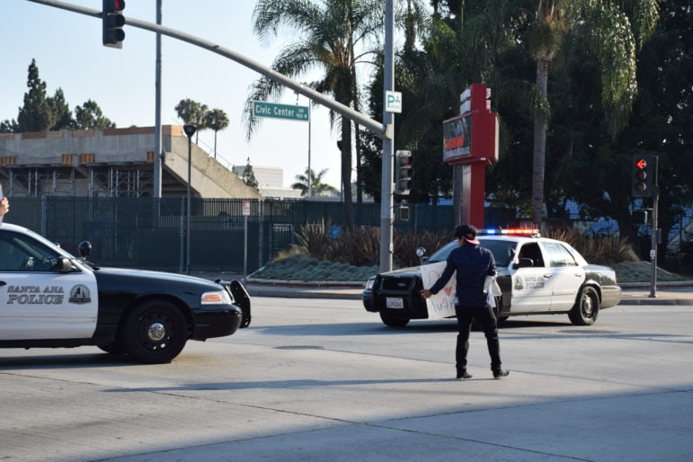 A protester confronts Santa Ana police on Civic Center Drive during march by immigration advocates.