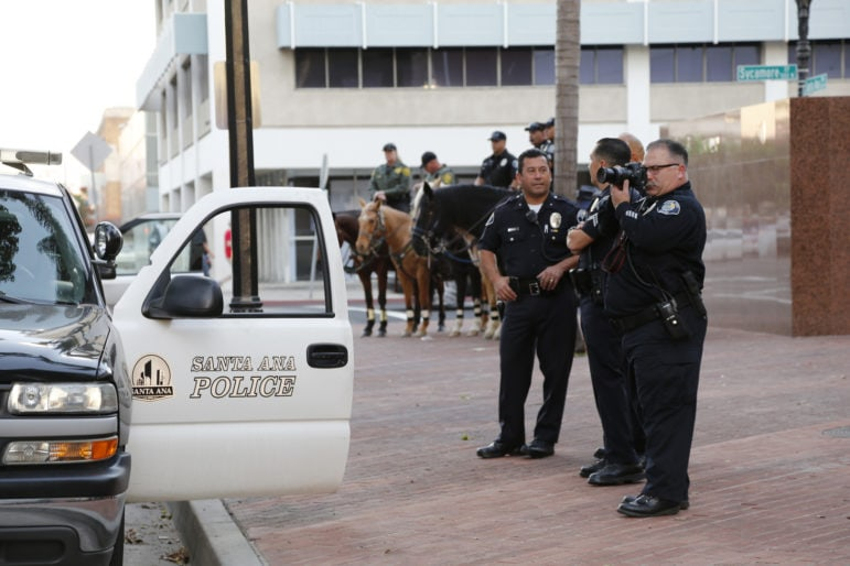 Santa Ana police monitor the rally at the old courthouse -- one officer takes photos of the crowd.