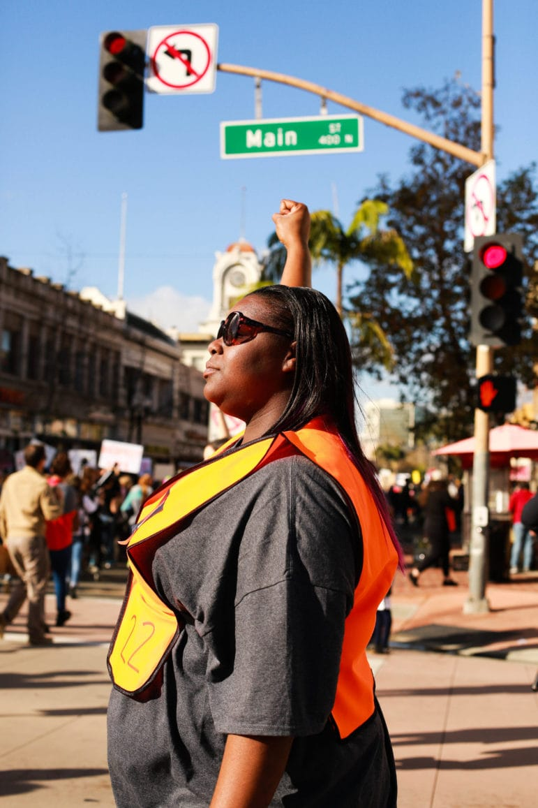 A woman holds her fist up in solidarity with fellow marchers.