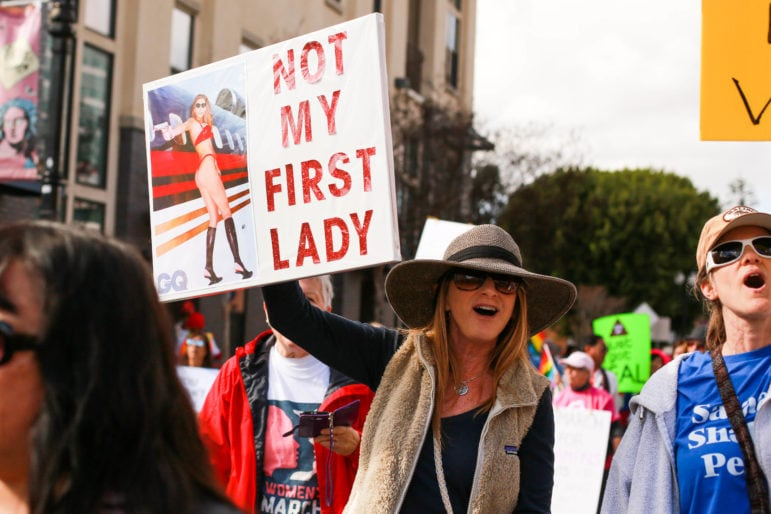 A marcher holds a sign with a photo of a bikini-clad Melania Trump before she became first lady.